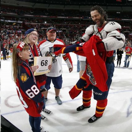 It's hard to figure out who is happier, the young lady getting the shirt or Jaromir Jagr removing it.